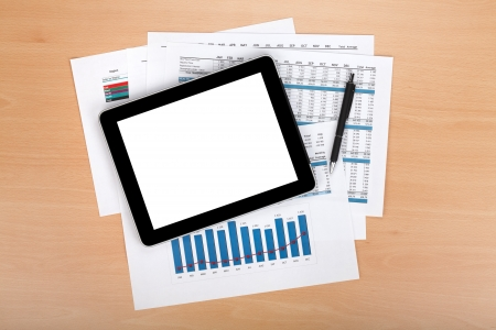 Tablet with blank screen over papers with numbers and charts. View from above photo