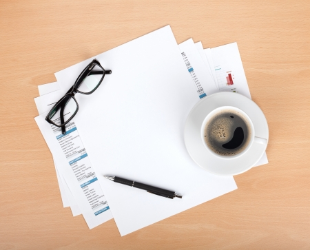 space to write: Blank paper with pen, glasses and coffee cup over financial documents