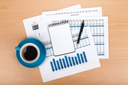 Blank notepad with pen and coffee cup over financial documents Stock Photo - 18483900