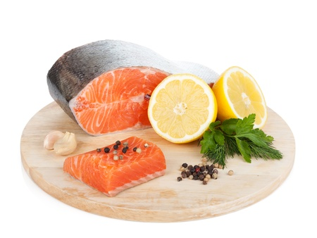 Salmon with herbs and lemon slices on cutting board  Isolated on white background photo