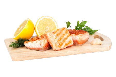 Grilled salmon with lemon and herbs on cutting board  Isolated on white background photo