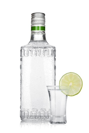 vodka bottle: Bottle of silver tequila and shot with lime slice. Isolated on white background