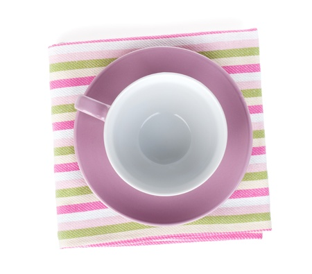 Violet coffee cup over kitchen towel. Isolated on white background photo