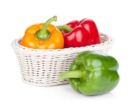 capsicums: Green, red and orange bell peppers in basket. Isolated on white background Stock Photo