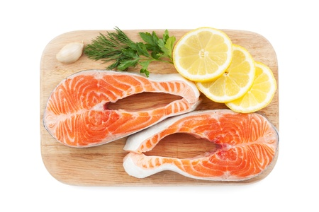 Salmon steaks with herbs and lemon slices on cutting board. Isolated on white background photo