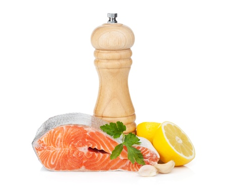 Salmon with herbs, pepper shaker and lemon. Isolated on white background photo