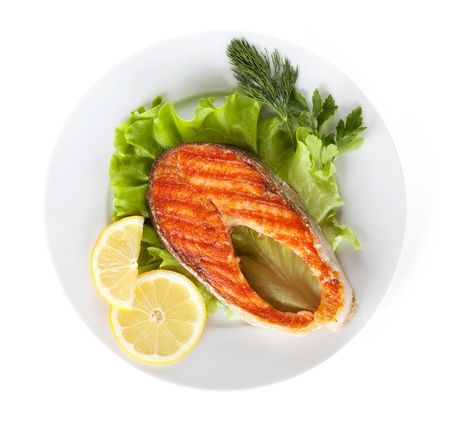 Grilled salmon with lemon slices and herbs on plate. Isolated on white background