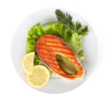 lemon slices: Salmone alla griglia con fette di limone e le erbe sulla piastra. Isolato su sfondo bianco Archivio Fotografico