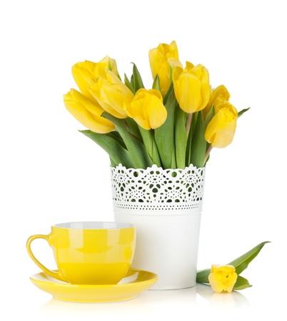 florero: Tulipanes de color amarillo y una taza de t�. Aislado en el fondo blanco