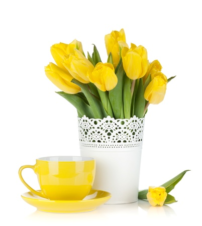 vase color: Yellow tulips and tea cup. Isolated on white background Stock Photo