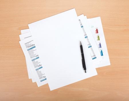trompo de madera: Papel en blanco con l�piz sobre los documentos financieros Foto de archivo
