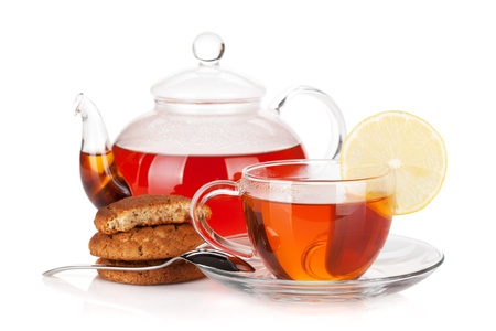 yellow tea pot: Glass cup and teapot of black tea with lemon and cookies. Isolated on white background