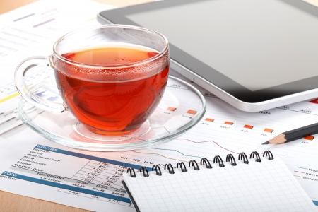 Tea cup on contemporary workplace with financial papers, office supplies and tablet photo