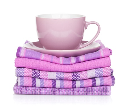 Coffee cup over kitchen towels  Isolated on white background photo