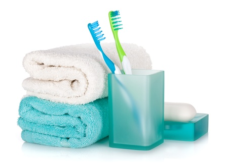 Toothbrushes, soap and two towels. Isolated on white background photo