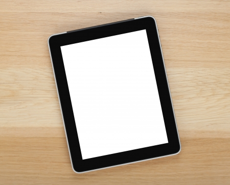 Touch screen tablet computer with blank screen on wooden table photo