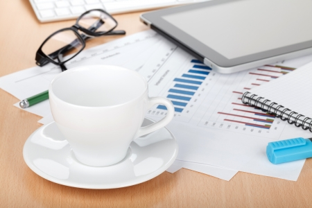Coffee cup on contemporary workplace with financial papers, computer, glasses and office supplies photo