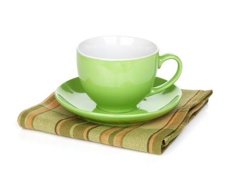 Coffee cup over kitchen towel. Isolated on white background photo