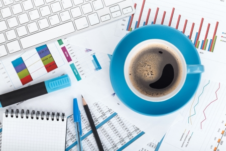 Blue coffee cup on financial papers, computer and office supplies photo