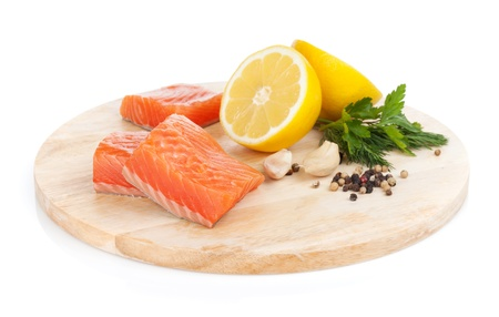 Salmon steaks on cutting board with lemons and herbs. Isolated on white background photo