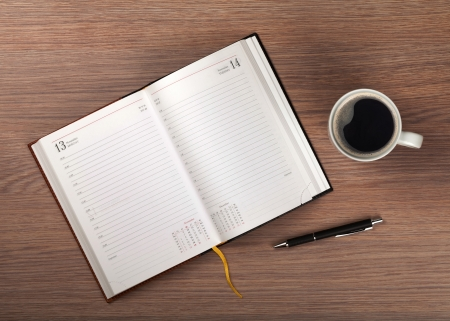 Notepad and coffee cup on wood table. View from above Stock Photo - 19896230