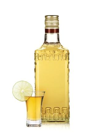 botella de licor: Botella de tequila de oro y le disparó con una rodaja de lima. Aislado en el fondo blanco