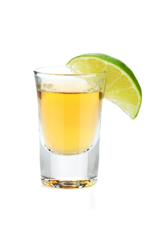 tequila: Shot of gold tequila with lime slice. Isolated on white background