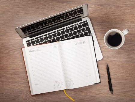Notepad, laptop and coffee cup on wood table. View from above Stock Photo - 19896323