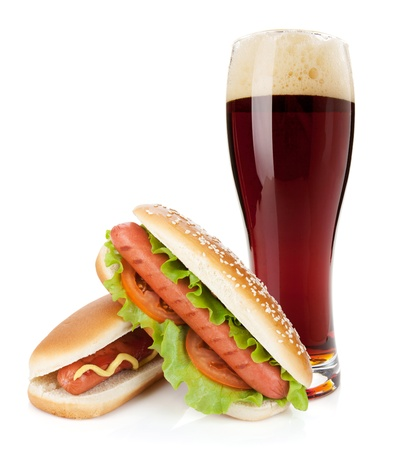 Dark beer glass and two hot dogs with various ingredients. Isolated on white background photo