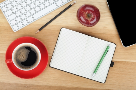 Coffee cup, red apple and office supplies on wooden table photo