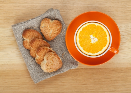Cup with orange and heart shaped cookies on wooden table. View from above photo