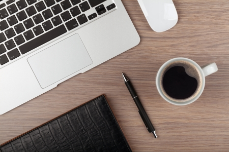 trabajaba: Bloc de notas, port?til y una taza de caf? en la mesa de madera. Vista desde arriba Foto de archivo