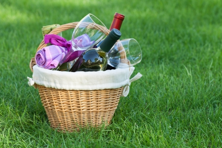 Outdoor picnic basket with wine bottles and glasses on lawn photo