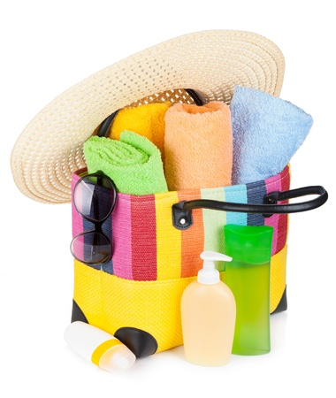 Bag with towels, sunglasses, hat and beach items. Isolated on white background photo