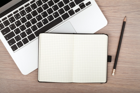 Notepad and laptop on wood table. View from above Stock Photo - 20238219