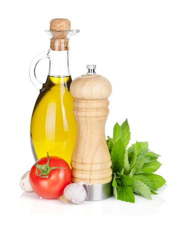 Fresh herbs, tomato, olive oil and pepper shaker. Isolated on white background photo