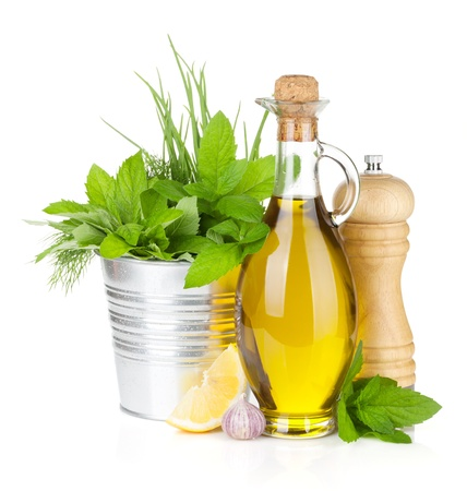 Fresh herbs, spices, olive oil and pepper shaker. Isolated on white background photo