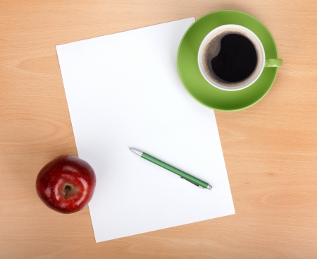 Blank paper with pen, coffee cup and red apple on wood table photo