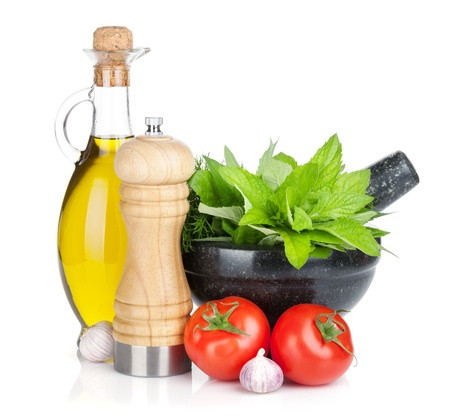 Fresh herbs, olive oil and pepper shaker  Isolated on white background photo