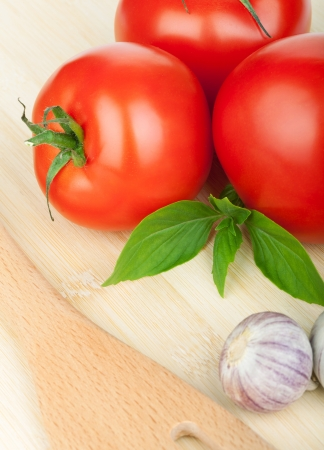 Three ripe tomatoes and basil on cutting board photo