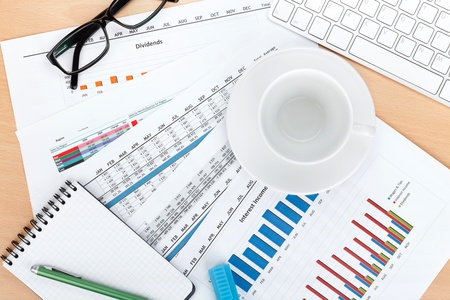Empty cup on contemporary workplace with financial papers and office supplies Stock Photo - 20619026