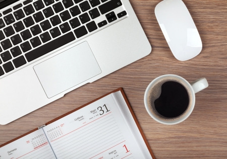 tabulka: Poznámkový blok, laptop a šálek kávy na dřevěném stole. Pohled shora