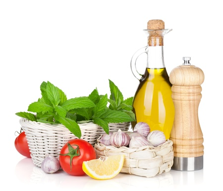 Fresh herbs, tomato, olive oil and pepper shaker  Isolated on white background photo