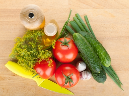 Ripe vegetables and knife on cutting board photo