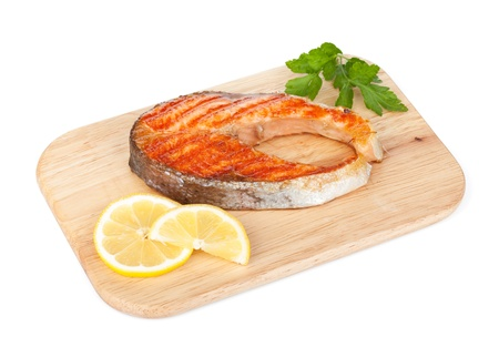 Grilled salmon with lemon and herbs on cutting board. Isolated on white background photo