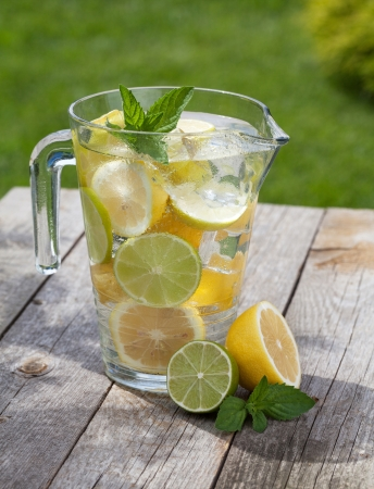Pitcher with homemade lemonade on wooden table photo