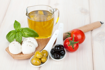 Mozzarella, olives, tomatoes and basil on wood table
