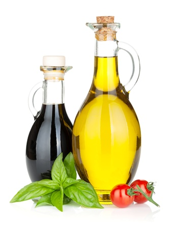 food dressing: Olive oil, vinegar bottles with basil and tomatoes. Isolated on white background