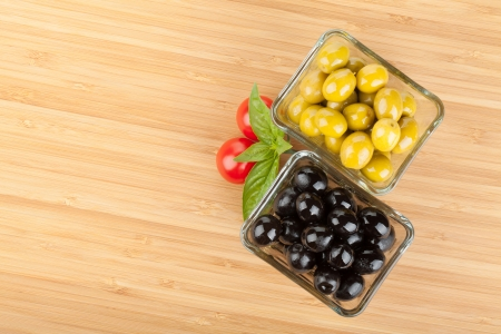 Olives, tomatoes and basil on cutting board with copyspace photo