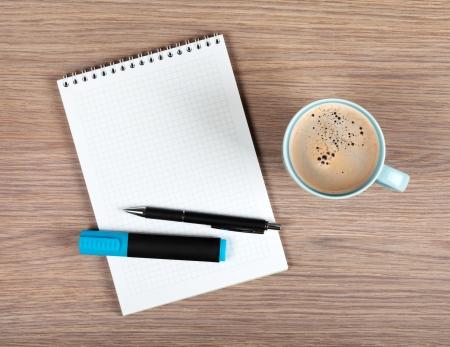 空白のメモ帳と木製のオフィスのテーブルの上にコーヒー カップ